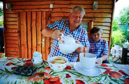 """Gary Blackburn, a 53-year-old tree surgeon from Lincolnshire, Britain, and his 11-year old son William are having tea time with typical British short bread at their British curiosities collection called """"Little Britain"""" in Linz-Kretzhaus, south of Germany's former capital Bonn, Germany, August 24, 2017. REUTERS/Wolfgang Rattay"""