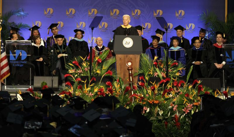 "Vice President Joe Biden, center, speaks during a graduation ceremony at the Miami Dade College in Miami, Saturday, May 3,2014. Biden said a ""constant, substantial stream of immigrants"" is important to the American economy, urging citizenship for immigrants living in the U.S. illegally. (AP Photo/Javier Galeano)"