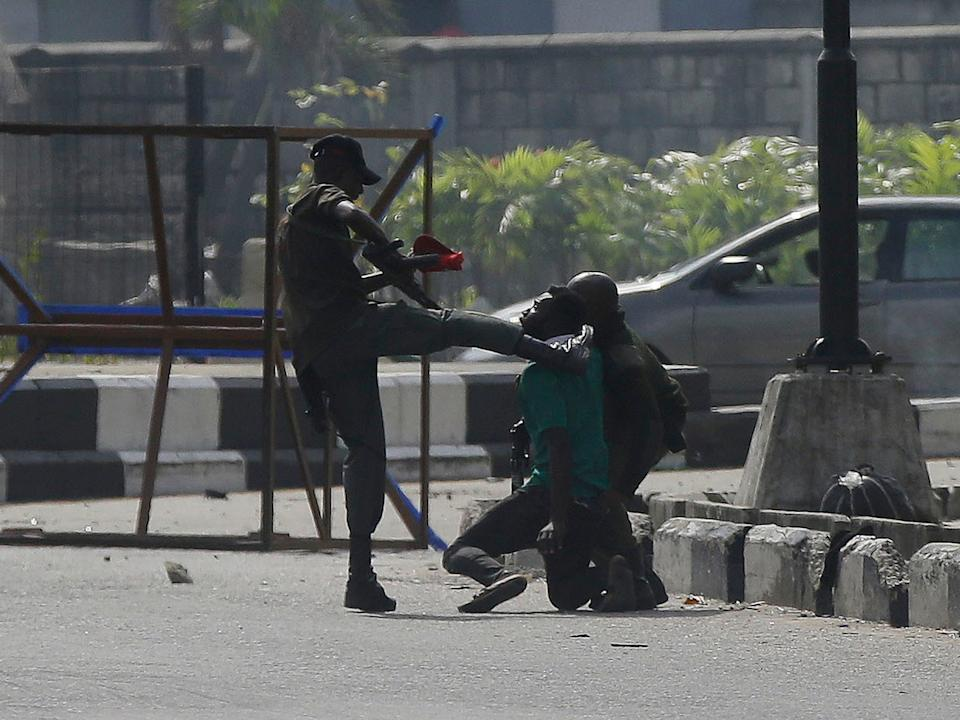 A police officer kicks a protester being detained by Lekki toll gate in Lagos on WednesdayAP
