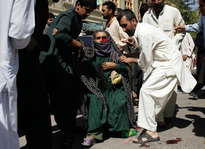 """FILE - In this Wednesday, Aug. 15, 2012 file photo, Afghans carry a wounded woman from the scene of an explosion in Herat, west of Kabul, Afghanistan. It was once President Barack Obama's """"war of necessity."""" Now, it's America's forgotten war. The Afghan conflict generates barely a whisper on the U.S. presidential campaign trail. It's not a hot topic at the office water cooler or in the halls of Congress _ even though 88,000 American troops are still fighting here and dying at a rate of one a day. (AP Photo/Hoshang Hashimi, File)"""