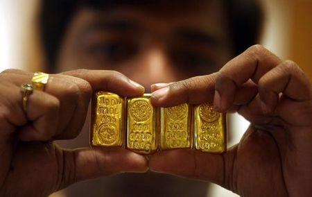 A salesman displays gold bars inside jewellery shop on the occasion of Akshaya Tritiya festival in Hyderabad