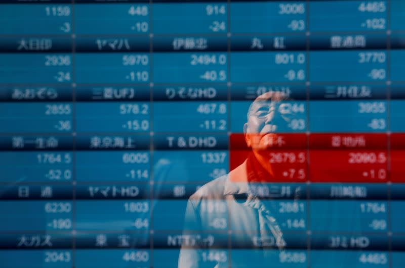 A man is reflected on a board showing stock prices outside a brokerage in Tokyo