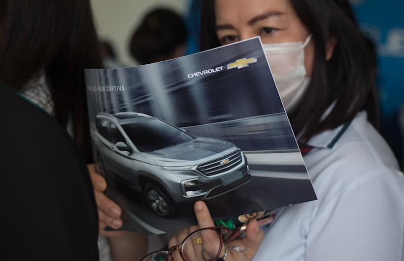 BANGKOK, THAILAND - 2020/02/19: A woman with a mask reads a brochure at the showroom. General Motors Company Limited and Chevrolet Sales announces the end of sales of Chevrolet vehicles in Thailand by the end of 2020, and offers reduced prices by 30-50% for Chevrolet vehicles. (Photo by Adisorn Chabsungnoen/SOPA Images/LightRocket via Getty Images)
