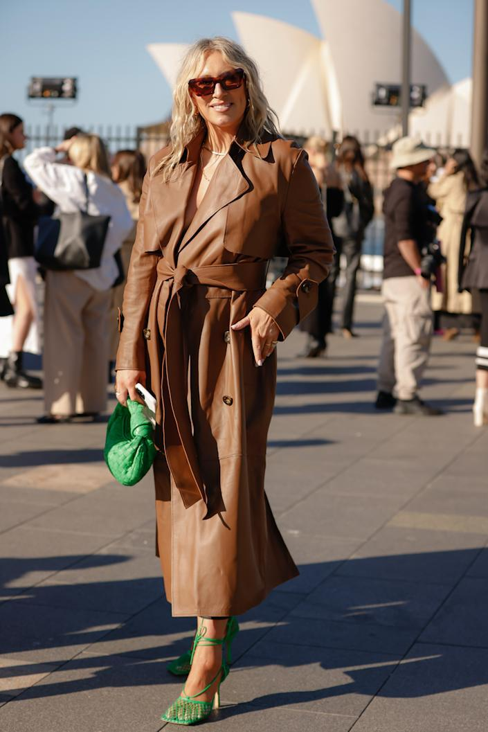 Phoebe Burgess wearing a camel coloured Camilla And Marc leather trench coat and Bottega Veneta green bag and shoes at Afterpay Australian Fashion Week 2021 on May 31, 2021 in Sydney, Australia