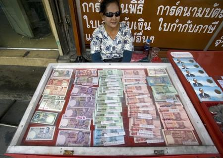File photo of a woman displaying Thai baht currency notes in Bangkok