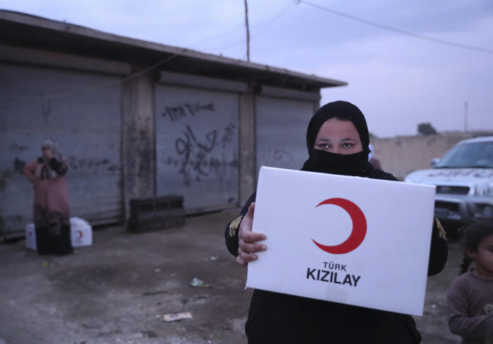 In this image provided by Turkish Red Crescent, a woman carries aid being distributed by Turkish Red Crescent in Ras Al-Ayn, Syria, Saturday, Oct. 19, 2019. Turkish Red Crescent says it has delivered humanitarian aid for 2000 people in Ras Al-Ayn, including flour with other food and hygiene materials to follow. The organisation said it also provided aid to Tal Abyad and will continue to do so in areas cleared by the Turkish and the Turkish-backed forces, from fighters from Kurdish People's Protection Units, or YPG. (Fatih Isci/Turkish Red Crescent via AP)