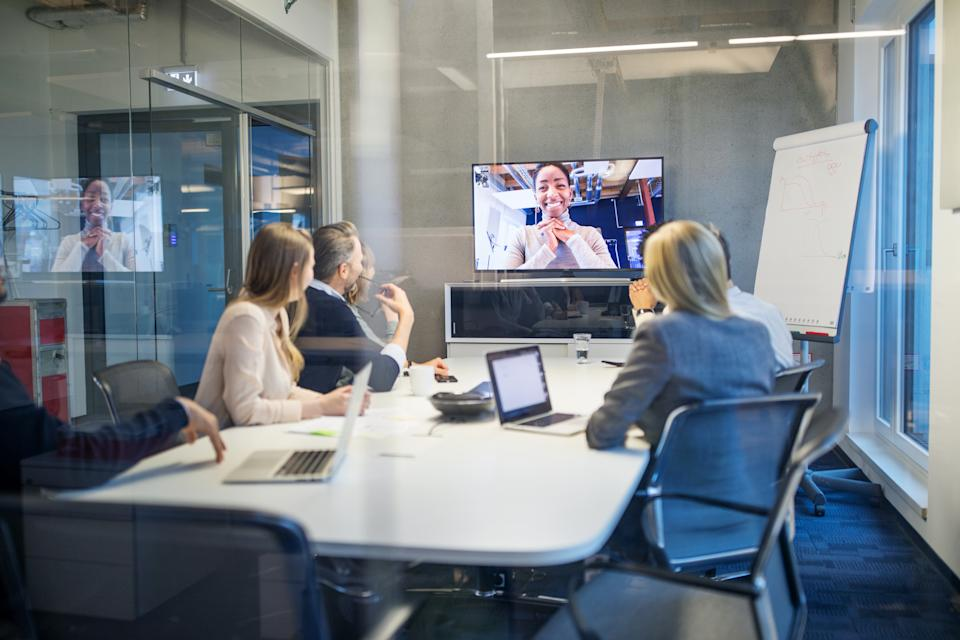 Business people looking at a screen during a video conference in the office. Businesswoman having video conference meeting with team sitting in board room.