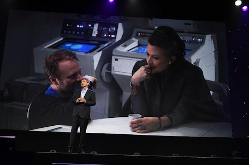 <p>Rian Johnson and Carrie Fisher provide the backdrop to Walt Disney Studios Chairman Alan Horn's introduction to the presentation. (Photo: Disney/Image Group LA) </p>
