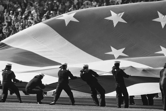 FILE - In this July 11, 1984 file photo, sailors struggle to control the giant flag used for opening ceremonies at the 55th All-Star game played in Candlestick Park, Tuesday, July 11, 1984, in San Francisco. The flag was unfurled at centerfield to accompany the Star Spangled Banner. Candlestick Park, known for its bone-numbing winds, the Catch and the earthquake-rocked 1989 World Series is officially closing after more than a half century of hosting sporting and cultural events. In a bow to historical symmetry, the Stick's finale will be a performance Thursday by Paul McCartney, 48 years after the Beatles' last scheduled concert lit up the venue. (AP Photo/Eric Risberg, File)
