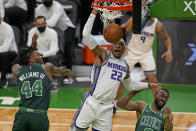 Sacramento Kings center Richaun Holmes (22) goes to the basket against Boston Celtics center Robert Williams III (44) and guard Kemba Walker, right, during the first quarter of an NBA basketball game Friday, March 19, 2021, in Boston. (AP Photo/Elise Amendola)