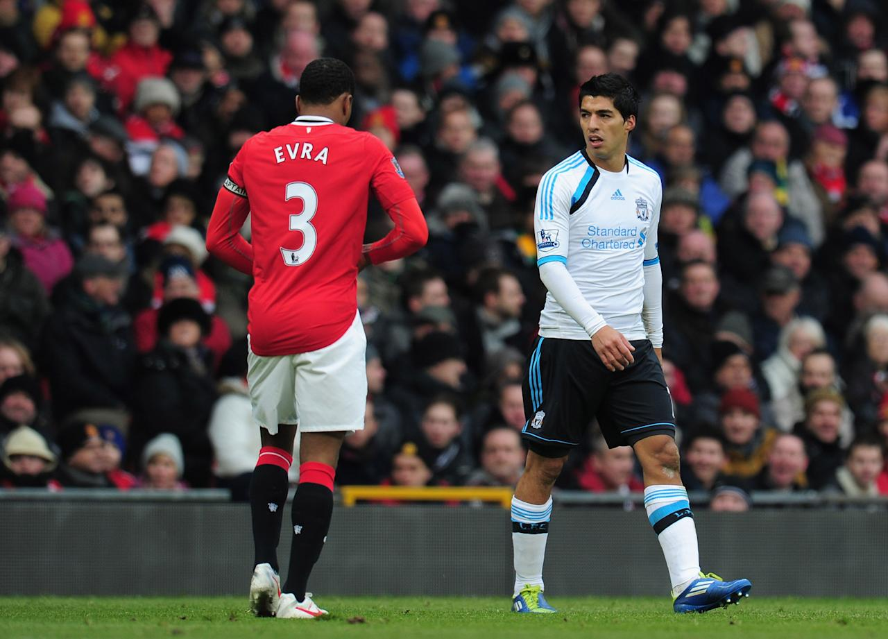 MANCHESTER, ENGLAND - FEBRUARY 11:  Luis Suarez of Liverpool looks at Patrice Evra of Manchester United during the Barclays Premier League match between Manchester United and Liverpool at Old Trafford on February 11, 2012 in Manchester, England.  (Photo by Shaun Botterill/Getty Images)