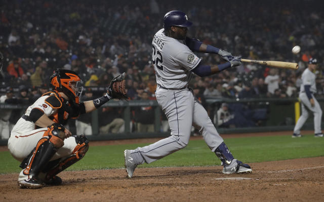 San Diego Padres' Franmil Reyes, right, hits a two-run home run in front of San Francisco Giants catcher Buster Posey during the seventh inning of a baseball game in San Francisco, Monday, April 8, 2019. (AP Photo/Jeff Chiu)