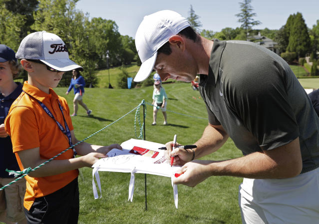 Rory McIlroy, of Northern Ireland, signs an autograph for a fan on the seventh hole during the pro-am of the Wells Fargo Championship golf tournament at Quail Hollow Club in Charlotte, N.C., Wednesday, May 2, 2018. McIlroy looks to bounce back after a disappointing performance at the Masters on one of his favorite courses, Quail Hollow Club. (AP Photo/Chuck Burton)