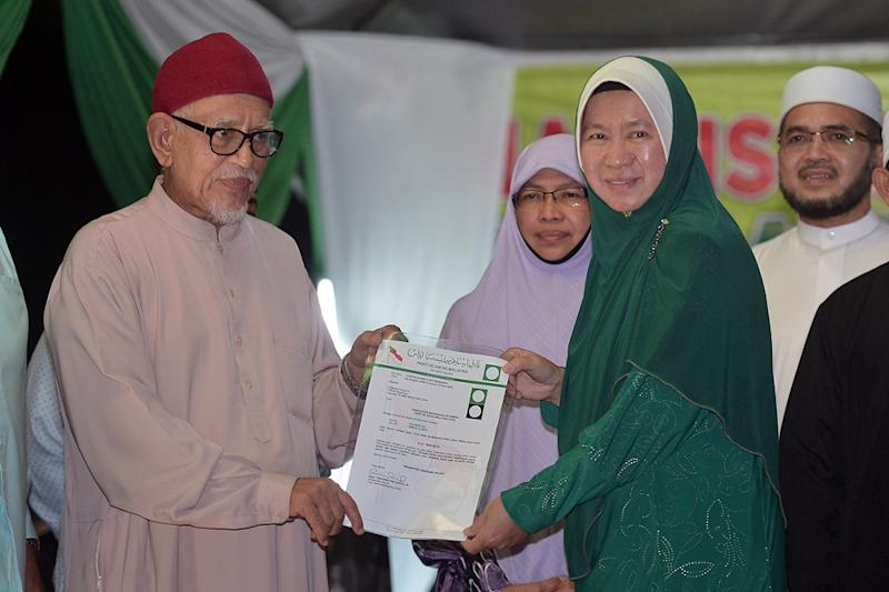 PAS president Datuk Seri Abdul Hadi Awang announces Dr Halimah Ali (right) as the party's candidate for the Seri Setia by-election in Petaling Jaya, August 15, 2018. — Picture by Mukhriz Hazim