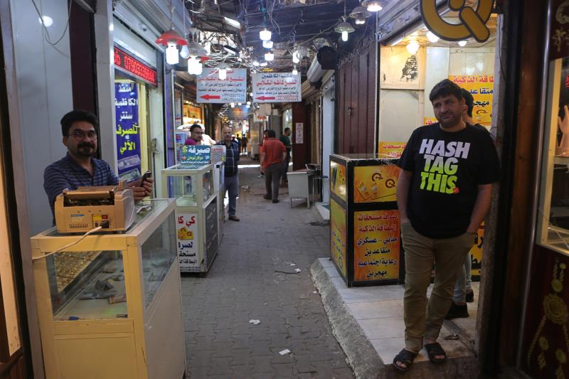 In this Wednesday, May 21, 2019, photo, money exchangers wait for customers at Shiite holy neighborhood of Kadhimiya's main market, Iraq. Many shop owners in the Shiite holy neighborhood of Kadhimiya, have seen their sales drop sharply over the past year since U.S. President Donald began reimposing sanctions on Iran, home to the largest number of Shiite Muslims around the world. (AP Photo/Khalid Mohammed)