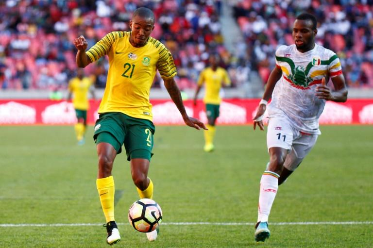 Thapelo Morena (L) of South Africa controls the ball with Lassina Coulibaly of Mali in pursuit