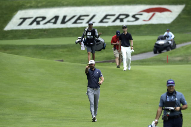Dustin Johnson, center, gestures as he walks toward his ball on the 15th fairway during the third round of the Travelers Championship golf tournament at TPC River Highlands, Saturday, June 27, 2020, in Cromwell, Conn. (AP Photo/Frank Franklin II)