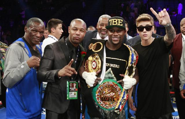 Floyd Mayweather Sr. (L), R&B singer Tank (2nd L), and singer Justin Bieber (R) celebrate Floyd Mayweather Jr.'s victory over WBC/WBA 154-pound champion Canelo Alvarez (not pictured) at the MGM Grand Garden Arena in Las Vegas, Nevada, September 14, 2013. Alvarez was previously undefeated in 42 fights. REUTERS/Steve Marcus (UNITED STATES - Tags: SPORT BOXING ENTERTAINMENT)