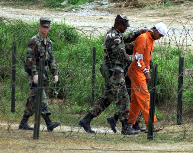 Military Police at camp X-Ray on the Naval Base at Guantanamo Bay, Cuba, bring a detainee to an interrogation room, February 6, 2002. There are one hundred and fifty eight detainees in Guantanamo Bay. Marc Serota/Reuters