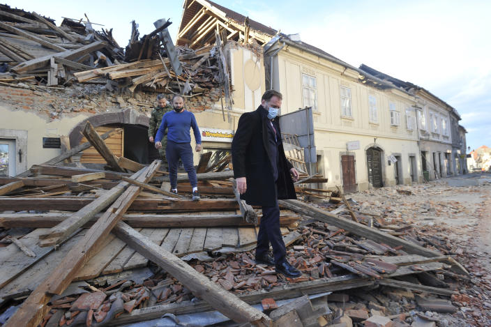 People move through remains of a building damaged in an earthquake, in Petrinja, Croatia, Tuesday, Dec. 29, 2020. A strong earthquake has hit central Croatia and caused major damage and at least one death in a town southeast of the capital. (AP Photo)