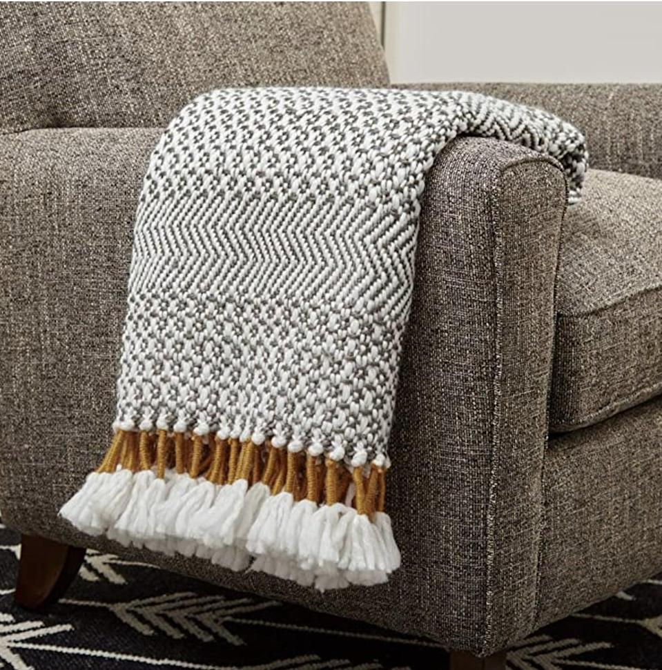 <p>This <span>Rivet Modern Hand-Woven Stripe Fringe Throw Blanket</span> ($52) will keep you cozy all day, every day.</p>