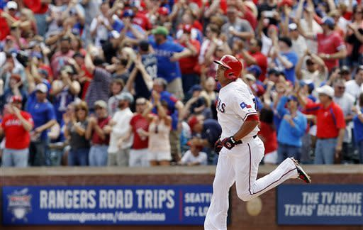 Fans cheer Texas Rangers' Nelson Cruz (17) as he rounds the bases after hitting a grand slam in the fifth inning of a baseball game against the Seattle Mariners in Arlington, Texas, Sunday, April 21, 2013. Texas won 11-3. (AP Photo/Brandon Wade)