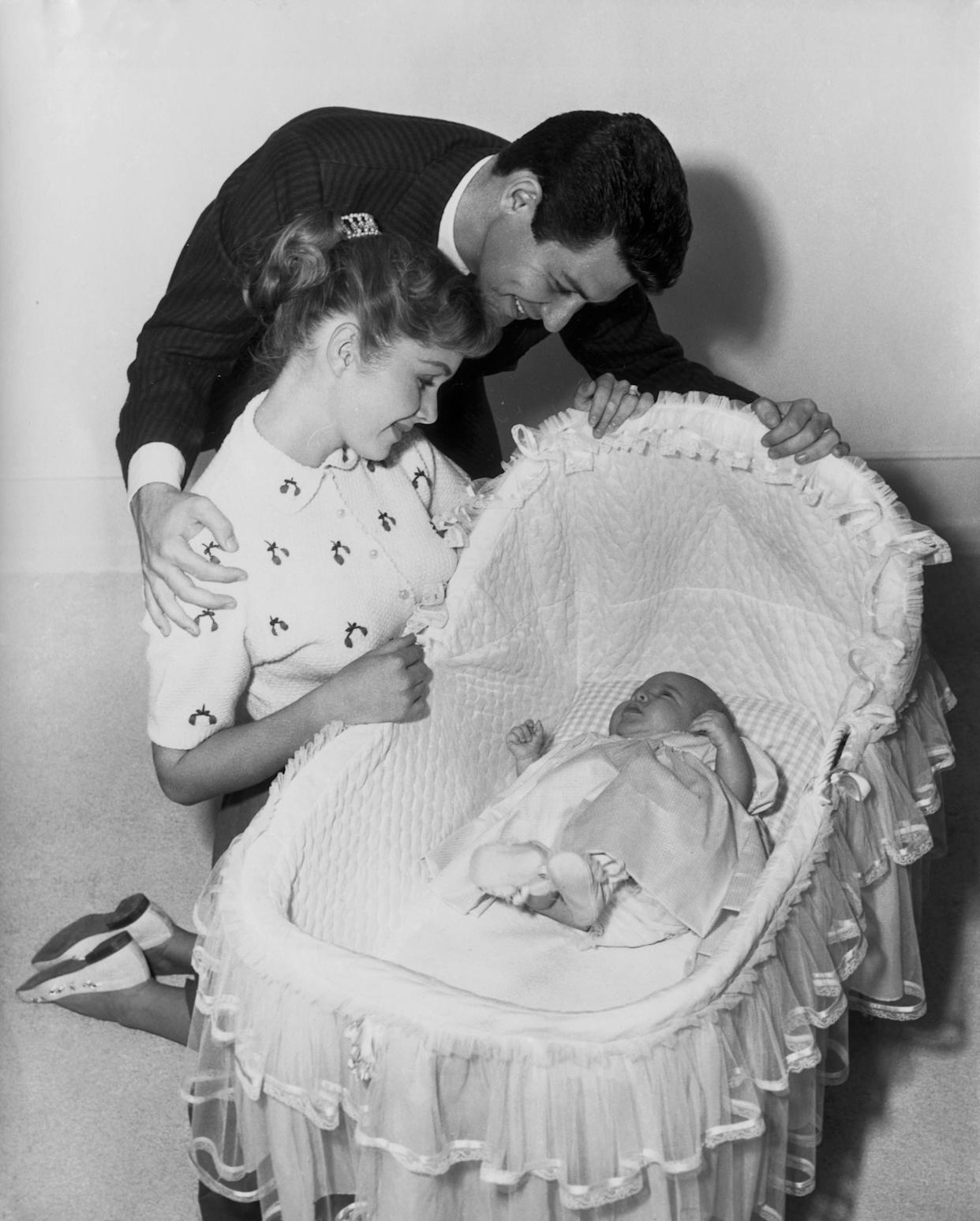 Carrie Frances Fisher was born on Oct. 21, 1956. Her father, Eddie Fisher, and mother, Debbie Reynolds, watch over her.