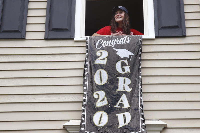 In this June 1, 2020 photo, high school graduate Lizzie Quinlivan poses at her home in Hingham, Mass. Quinlivan has opted to attend closer-to-home Georgetown instead of colleges on the west coast which were on her original wish-list. As students make college plans for this fall, some U.S. universities are seeing surging interest from in-state students looking to stay closer to home amid the coronavirus pandemic.  (AP Photo/Elise Amendola)