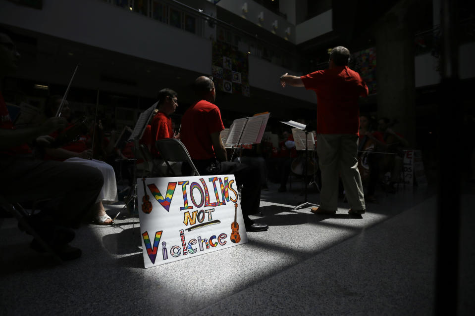 Conductor William Scheible directs a farewell concert with music teachers slated to loose their jobs and former students at the Philadelphia school district's headquarters, Monday, June 24, 2013, in Philadelphia. Education advocates are doing everything they can to draw attention to the dire situation in the city's public schools, which are facing a $304 million deficit. (AP Photo/Matt Slocum)