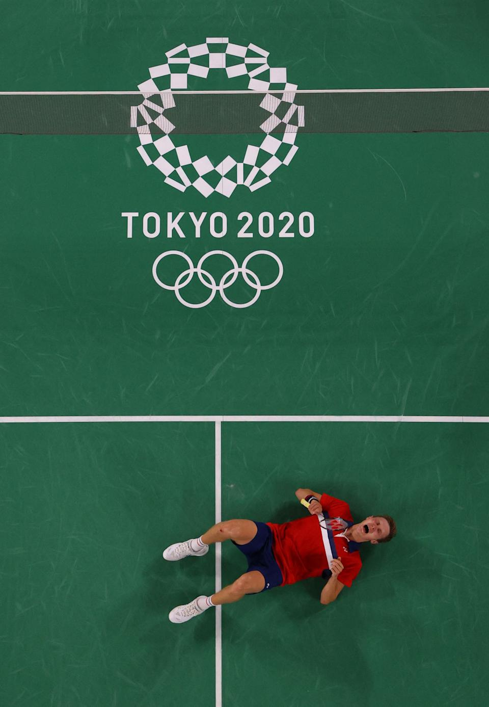 <p>Denmark's Viktor Axelsen celebrates after beating China's Chen Long to win their men's singles badminton final match during the Tokyo 2020 Olympic Games at the Musashino Forest Sports Plaza in Tokyo on August 2, 2021. (Photo by LINTAO ZHANG / POOL / AFP) (Photo by LINTAO ZHANG/POOL/AFP via Getty Images)</p>