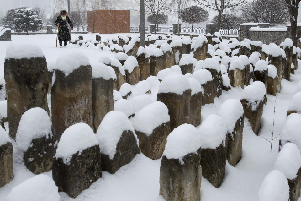 An elderly Chechen man walks to pray at a snow-covered cemetery, a memorial to the Stalin-era deportation's victims, in Grozny, Russia, Friday, March 12, 2021. Chechens and Ingush were victims of the 1944 deportations to the barren steppes of then-Soviet Central Asia. (AP Photo/Musa Sadulayev)