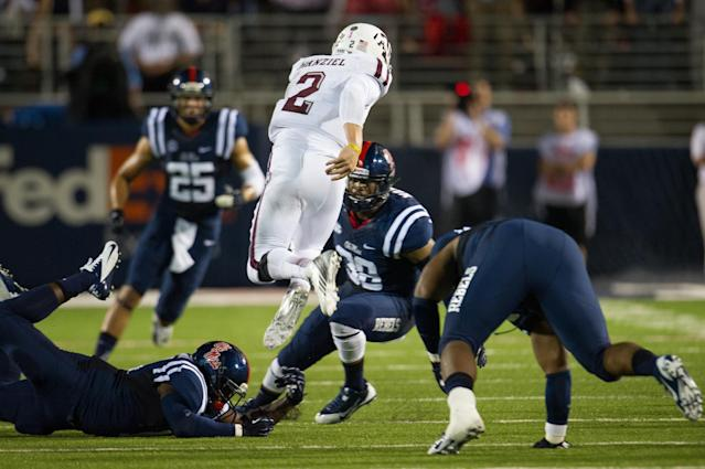 OXFORD, MS - OCTOBER 12: Quarterback Johnny Manziel #2 of the Texas A&M Aggies leaps over linebacker Serderius Bryant #14 of the Ole Miss Rebels during the first half of play on October 12, 2013 at Vaught-Hemingway Stadium in Oxford, Mississippi. At halftime Texas A&M leads Ole Miss 14-10. (Photo by Michael Chang/Getty Images)