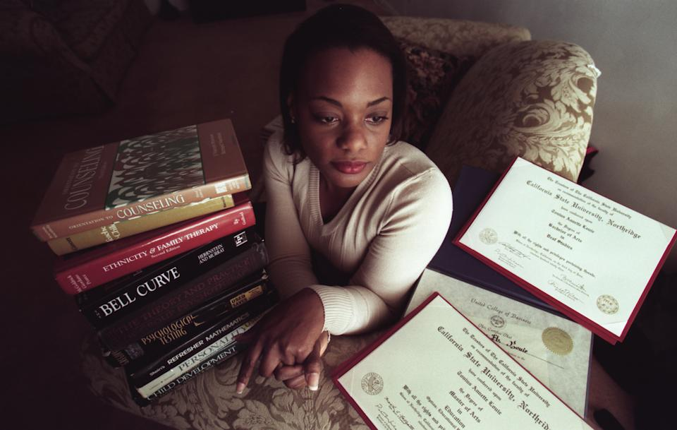 Tonius Louie, 34, of Hollywood, now a grad student, with some of her books and degrees she has earned while racking up a $70,000 debt in school loans. (Photo by David Bohrer/Los Angeles Times via Getty Images)