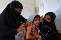 FILE PHOTO: A student reacts as she gets a free anti-typhoid vaccine during the immunisation campaign at a school in Karachi