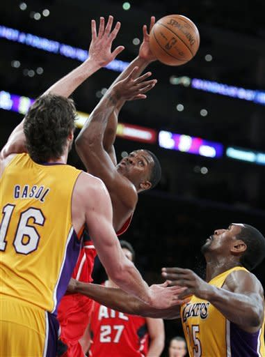 Los Angeles Lakers forwards Pau Gasol (16), of Spain, and Metta World Peace (15) defend against a pass by Atlanta Hawks guard Joe Johnson, second from left, during the first half of an NBA basketball game in Los Angeles, Tuesday, Feb. 14, 2012. (AP Photo/Alex Gallardo)