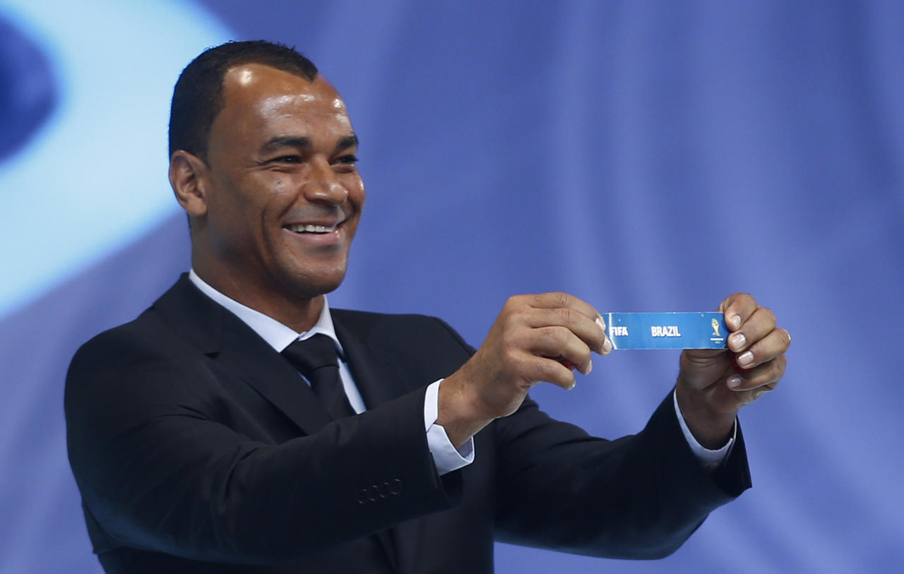Former soccer great and World Cup winner Cafu from Brazil holds the ticket of Brazil during the draw ceremony for the 2014 soccer World Cup in Costa do Sauipe near Salvador, Brazil, Friday, Dec. 6, 2013. (AP Photo/Victor R. Caivano)