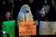 """A demonstrator dressed as a polar bear holds a placard reading """"humans can do better"""""""