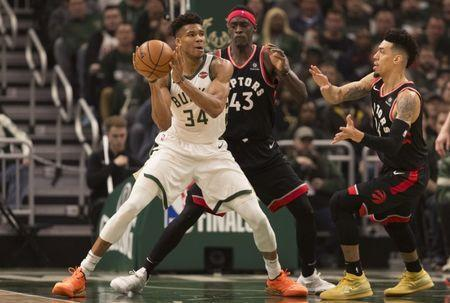 May 17, 2019; Milwaukee, WI, USA; Milwaukee Bucks forward Giannis Antetokounmpo (34) passes the ball under pressure from Toronto Raptors forward Pascal Siakam (43) and guard Danny Green (14) during the first quarter in game two of the Eastern conference finals of the 2019 NBA Playoffs at Fiserv Forum. Mandatory Credit: Jeff Hanisch-USA TODAY Sports