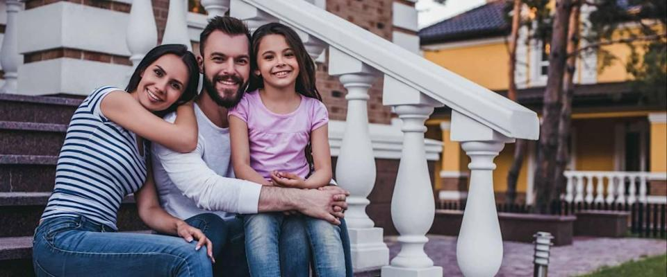 Happy family is sitting on porch of their modern private house, smiling and looking at camera.