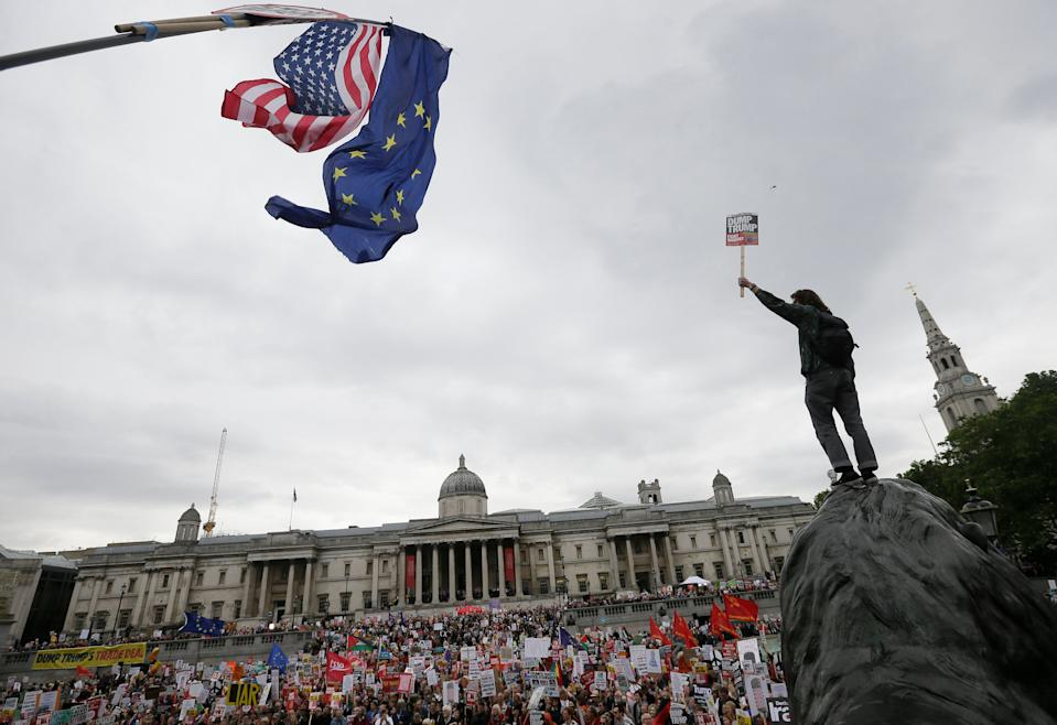Man holding up a sign stand on a statue as people gather in Trafalgar Square, central London, to demonstrate against the state visit of President Donald Trump, June 4, 2019. (Photo: Tim Ireland/AP)