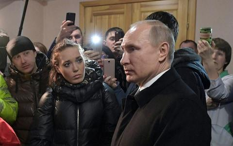 Russian President Vladimir Putin listens to locals and relatives of the victims - Credit: Alexei Druzhinin
