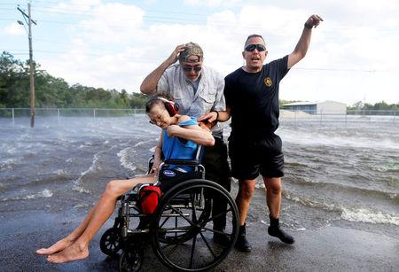 FILE PHOTO:  Phil Haberman gestures to a helicopter and rescue personnel while Rocky Breaux helps Hersey Kirk as she waits to be air lifted after being rescued from her home flooded by Tropical Storm Harvey in Rose City