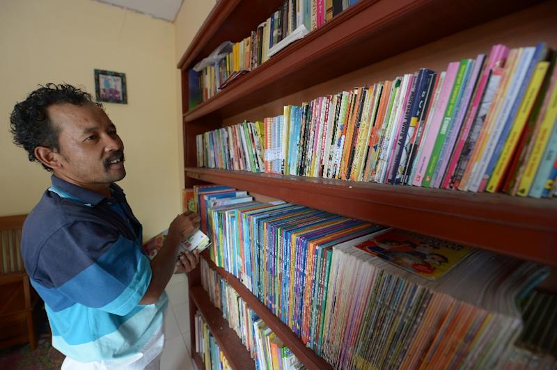 Ridwan Sururi, who runs a mobile library on horseback, selects books for villagers to read in Serang (AFP Photo/Adek Berry)