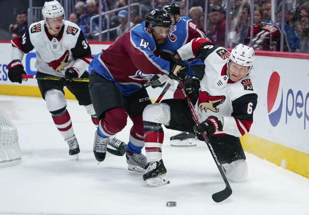 Arizona Coyotes defenseman Jakob Chychrun (6) shoots from a knee as Colorado Avalanche left wing Pierre-Edouard Bellemare (41) connects during the first period of an NHL hockey game, Saturday, Oct. 12, 2019, in Denver. (AP Photo/Jack Dempsey)