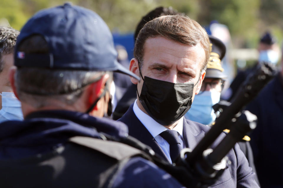French President Emmanuel Macron speaks with a police officer during a visit on the strengthening border controls at the crossing between Spain and France, at Le Perthus, France, Thursday, Nov. 5, 2020. (Guillaume Horcajuelo, Pool via AP)