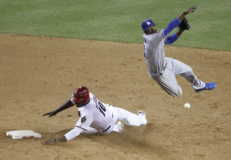 Los Angeles Dodgers shortstop Dee Gordon, right, leaps to avoid the slide by Arizona Diamondbacks' Justin Upton, left, to complete a double play for the final outs of the game in the ninth inning of a baseball game Tuesday, May 22, 2012, in Phoenix. The Dodgers won 8-7.(AP Photo/Paul Connors)
