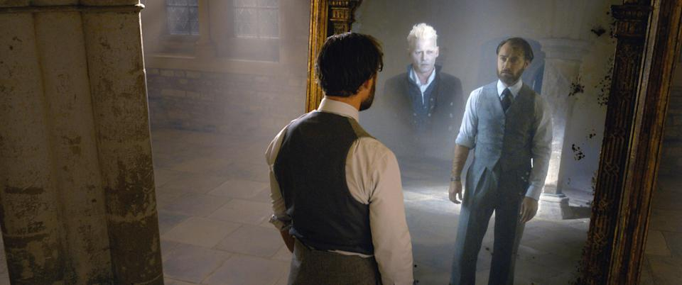 Dumbledore (Jude Law) sees his heart's desire, Grindelwald (Johnny Depp) reflected in the Mirror of Erised in <em>Fantastic Beasts: The Crimes of Grindelwald</em> (Photo: Warner Bros. Entertainment Inc./Courtesy Everett Collection)