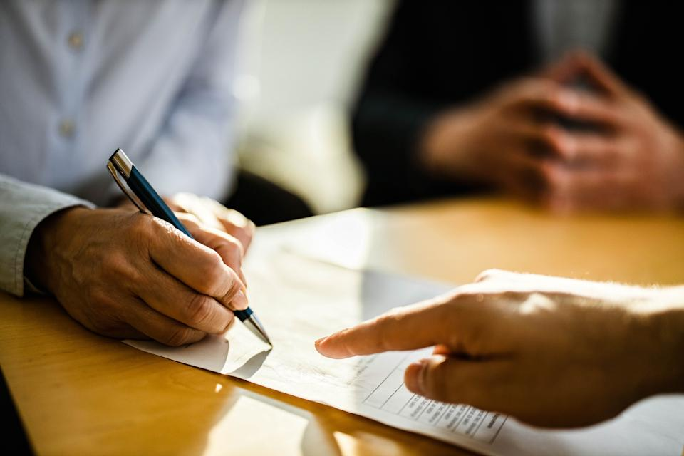 Close up of unrecognizable female person signing a contract on a meeting with agent.