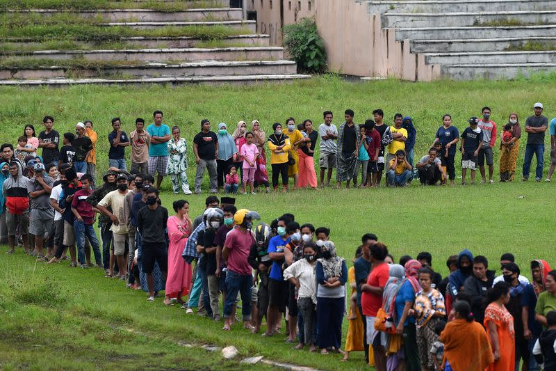 People stand in line for aid assistance at the Manakarra stadium following an earthquake in Mamuju