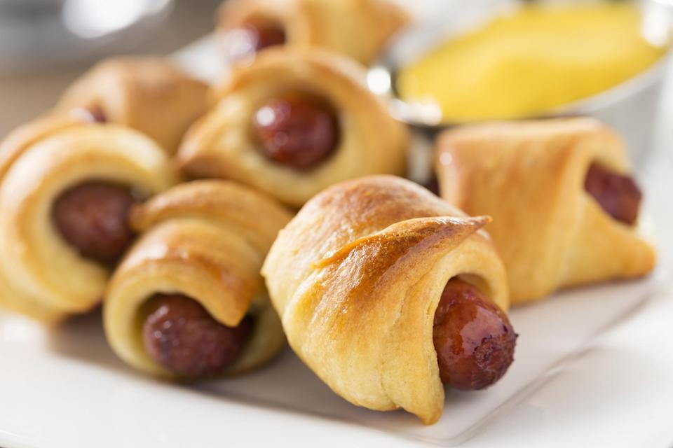 """<p>Convenience products like frozen puff pastry are a lifesaver for the holiday season. Pigs in a blanket are the easiest appetizer in the world to make, and they're always a crowd-pleaser.</p> <p><em><a href=""""https://www.thedailymeal.com/recipes/everything-bagel-pigs-blanket-recipe?referrer=yahoo&category=beauty_food&include_utm=1&utm_medium=referral&utm_source=yahoo&utm_campaign=feed"""" rel=""""nofollow noopener"""" target=""""_blank"""" data-ylk=""""slk:For the Everything Bagel Pigs in a Blanket recipe, click here."""" class=""""link rapid-noclick-resp"""">For the Everything Bagel Pigs in a Blanket recipe, click here.</a></em></p>"""
